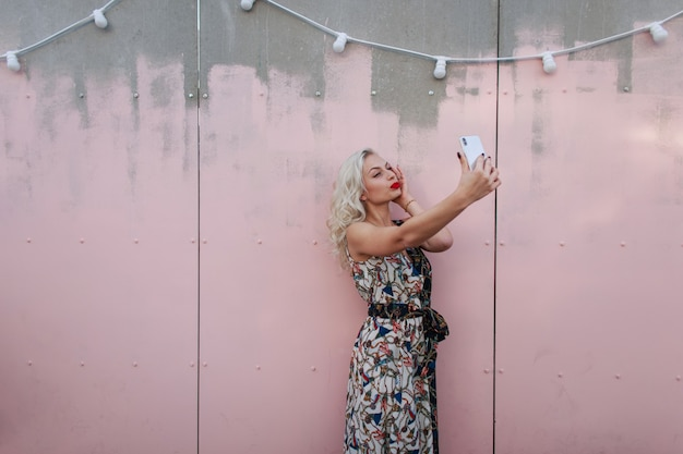 Piękna młoda kobieta w modnej sukience vintage robi zdjęcie na telefon na ulicy w pobliżu różowej ściany