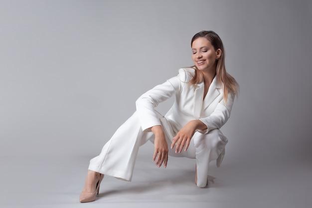 Piękna młoda kobieta w modnym białym garniturze i beżowych butach na wysokim obcasie