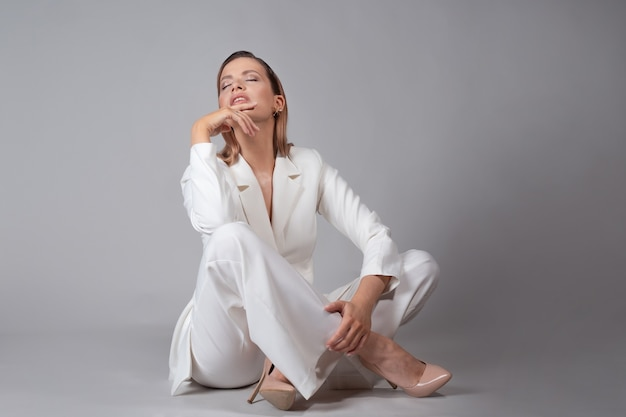 Piękna młoda kobieta w modnym białym garniturze i beżowych butach na wysokim obcasie,