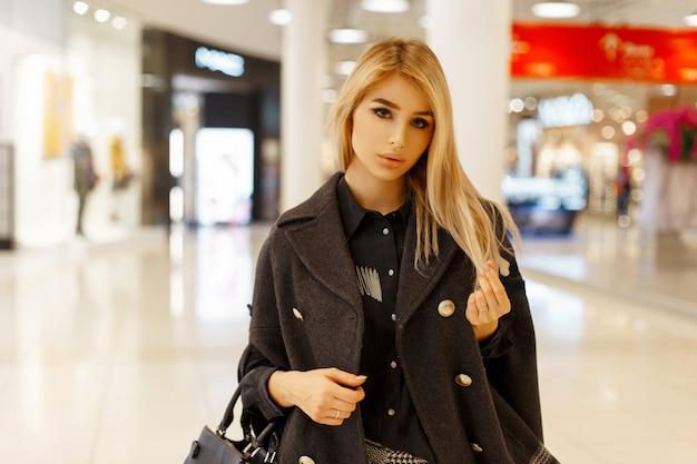 Piękna młoda kobieta w modnym stylowym płaszczu z torebką w centrum handlowym