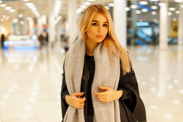 Piękna młoda kobieta w modnym szarym płaszczu ze stylowym szalikiem w centrum handlowym