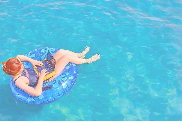 Piękna młoda kobieta w morzu z laptopem