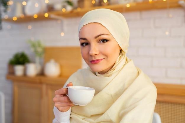 Piękna młoda kobieta w muzułmańskiej chustce w kuchni przy filiżance napoju