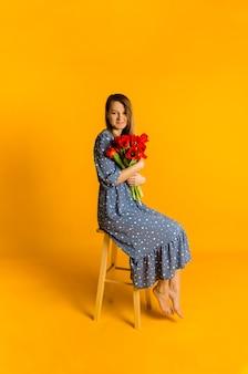 Piękna młoda kobieta w niebieskiej sukience w kropki z bukietem czerwonych tulipanów siedzi na krześle na żółtej ścianie