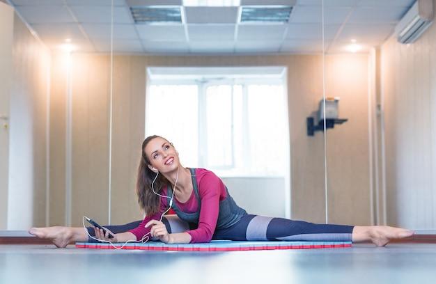 Piękna młoda kobieta w odzieży sportowej ze słuchawkami, słuchanie muzyki i rozciąganie mięśni.