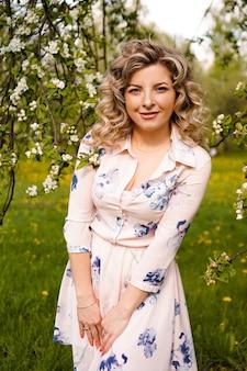 Piękna młoda kobieta w ogrodzie jabłkowym w słoneczny dzień wiosny - szczęśliwe chwile