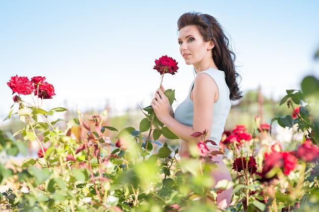 Piękna młoda kobieta w ogrodzie z różami