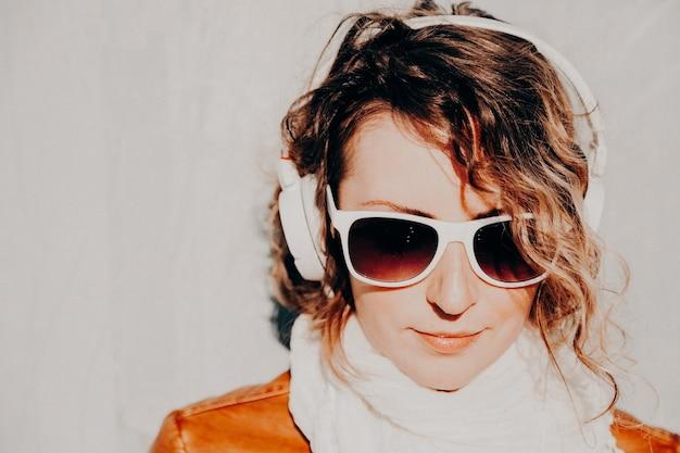 Piękna młoda kobieta w okularach przeciwsłonecznych i słuchawkach, słuchając muzyki stojącej przy ścianie. koncepcja stylu casual.