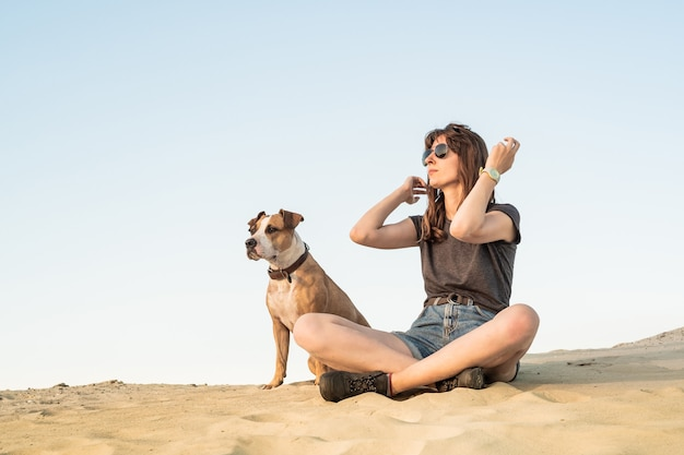 Piękna młoda kobieta w okularach przeciwsłonecznych z psem siedzieć na piasku. dziewczyna w ubranie turystyczne i szczeniak staffordshire terrier siedzi na piaszczystej plaży lub na pustyni w gorący słoneczny dzień