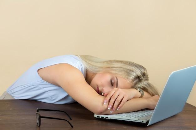 Piękna młoda kobieta w okularach śpi na laptopie