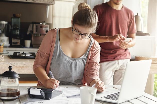 Piękna młoda kobieta w okularach wygląda poważnie, zapisując długopisem, zarządzając podatkami i obliczając rachunki, próbując zmniejszyć wydatki domowe, aby zaoszczędzić pieniądze i pozwolić sobie na duży zakup