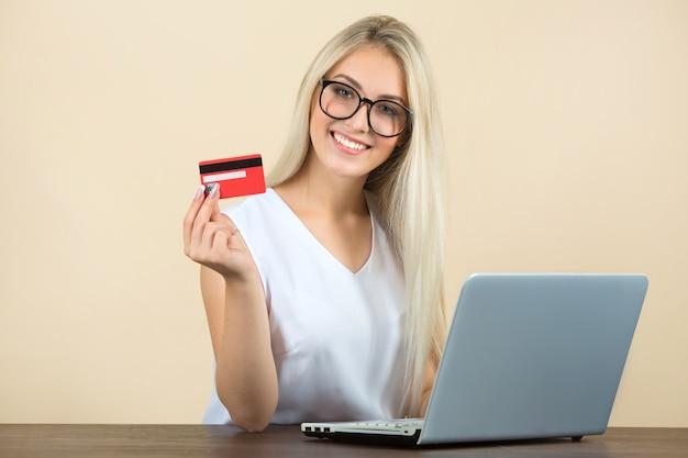 Piękna młoda kobieta w okularach z laptopem z kartą kredytową