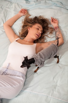Piękna młoda kobieta w piżamie, spanie w łóżku w nocy. mały pies.