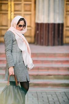 Piękna młoda kobieta w płaszcz ze stawianiem torby