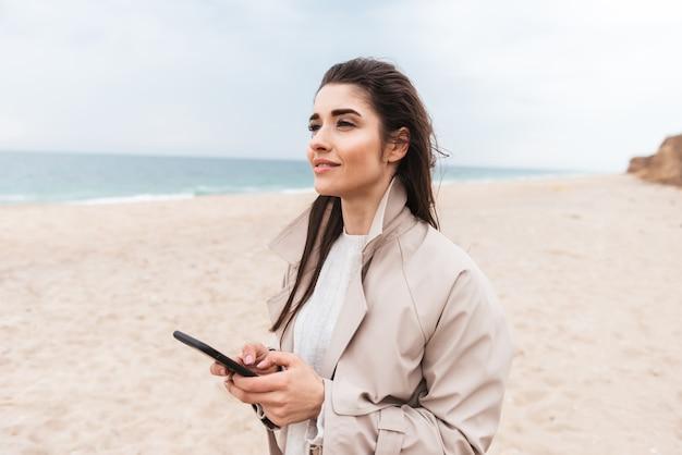 Piękna młoda kobieta w płaszczu spacerująca nad morzem, korzystająca z telefonu komórkowego