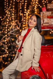 Piękna młoda kobieta w pobliżu retro czerwony samochód z lampkami choinkowymi.
