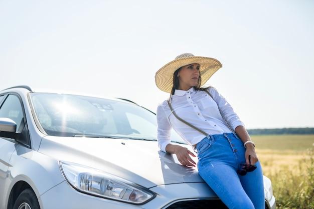 Piękna młoda kobieta w pobliżu samochodu, który zaparkował na poboczu drogi. przyjemność podróżowania.
