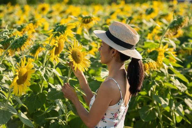Piękna młoda kobieta w polu słoneczników w białej sukni. podróż na koncepcji weekendu. portret autentycznej kobiety w słomkowym kapeluszu. na zewnątrz na polu słonecznika.