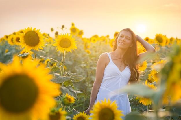 Piękna młoda kobieta w polu słoneczników w białej sukni