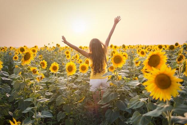 Piękna młoda kobieta w polu słoneczników