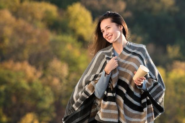 Piękna młoda kobieta w poncho z kawą