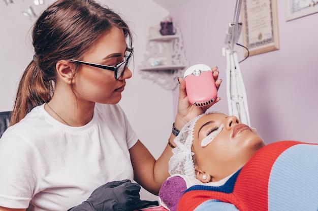Piękna młoda kobieta w procedurze przedłużania rzęs. koncepcja kosmetyków i pielęgnacji ciała.