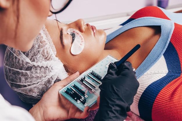 Piękna młoda kobieta w procedurze przedłużania rzęs. kosmetyki i pielęgnacja ciała z bliska strzał.