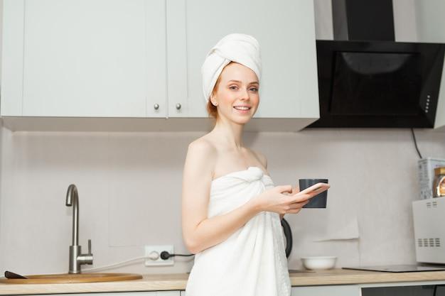 Piękna młoda kobieta w ręcznik z kubkiem i telefonem komórkowym w kuchni