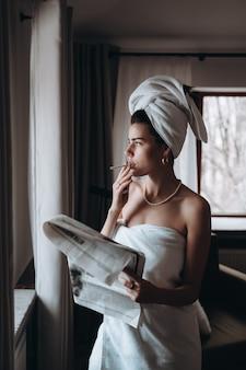 Piękna młoda kobieta w ręczniku pali papierosa i czyta gazetę