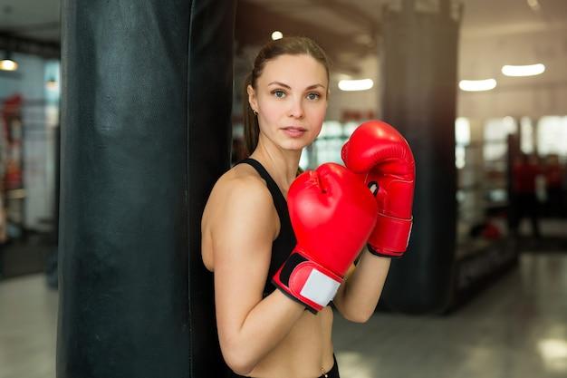Piękna młoda kobieta w rękawice bokserskie w pobliżu worek treningowy na siłowni w treningu