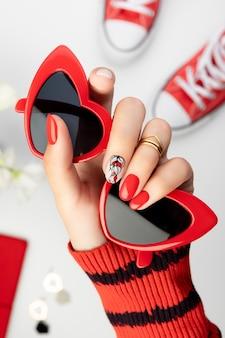 Piękna młoda kobieta w rękę z czerwonym manicure na szarym tle