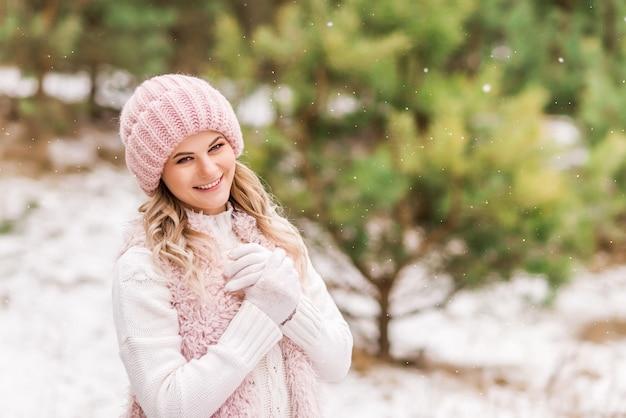 Piękna młoda kobieta w różowej kurtce i kapeluszu, uśmiechając się w zimowym lesie.
