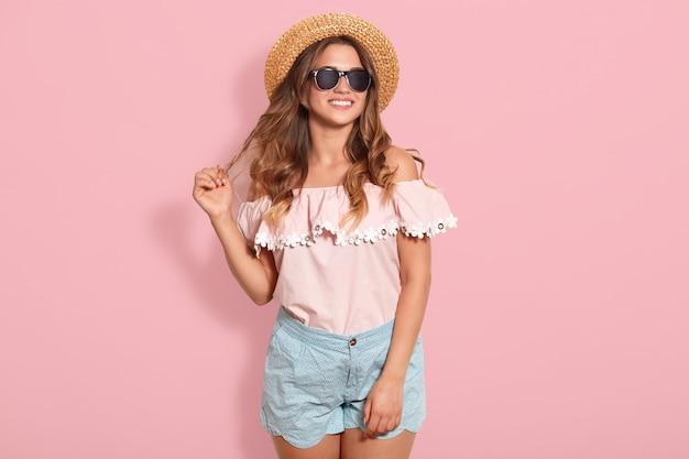 Piękna młoda kobieta w różowej letniej bluzce, niebieskiej krótkiej, okularach przeciwsłonecznych i kapeluszu przeciwsłonecznym, odsuwając włosy na bok, będąc w dobrym nastroju, gotowa na wyjście z przyjaciółmi.