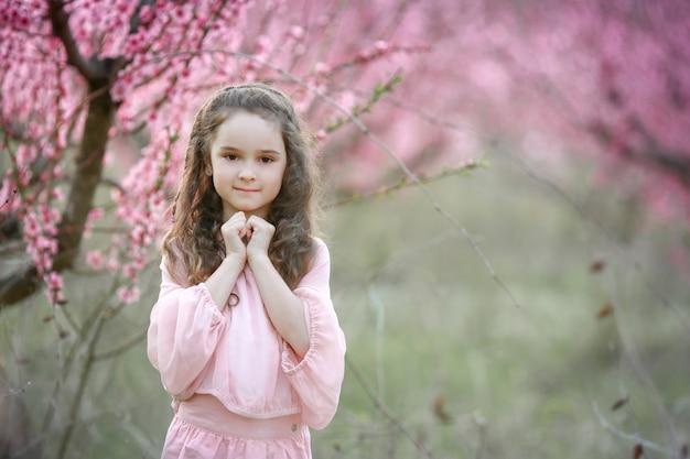 Piękna młoda kobieta w różowej sukience ogrodowej kwitnących sakura