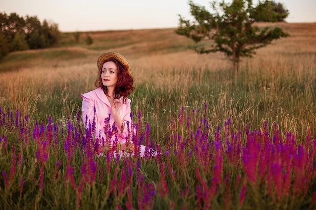 Piękna młoda kobieta w różowej sukience vintage i słomkowym kapeluszu w polne kwiaty (szałwia, szałwia)