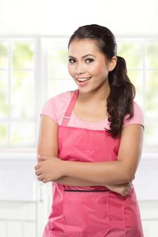 Piękna młoda kobieta w różowym fartuchu