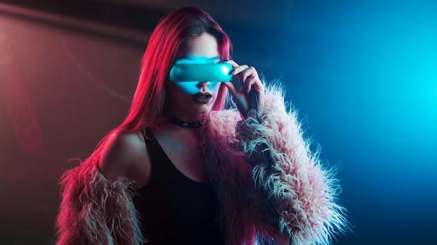Piękna młoda kobieta w rzeczywistości wirtualnej, styl cyberpunk, neonowe światło, koncepcja vr