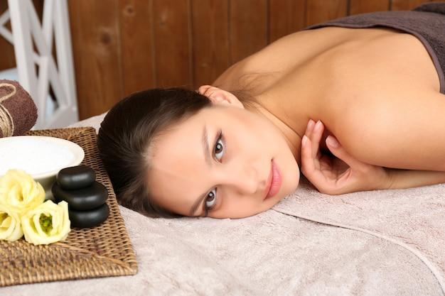 Piękna młoda kobieta w salonie spa na drewnianej ścianie