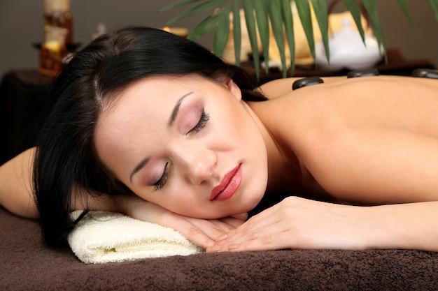 Piękna młoda kobieta w salonie spa z kamieniami spa, w ciemności