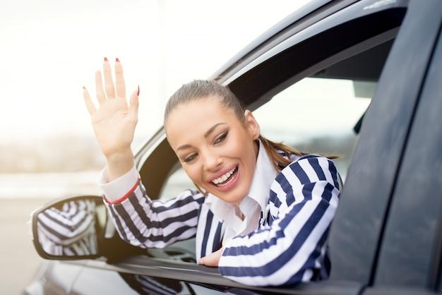 Piękna młoda kobieta w samochodzie, machając przez okno i uśmiechając się.
