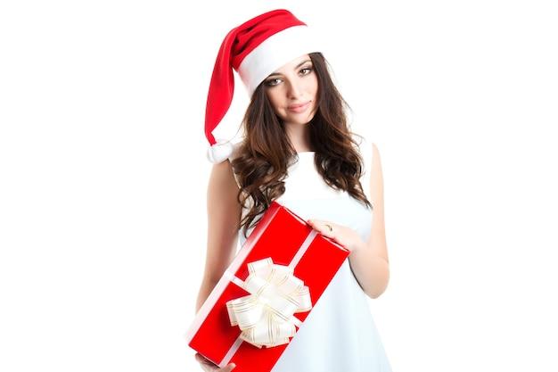 Piękna młoda kobieta w santa hat trzyma białe pudełko w ręku z czerwoną wstążką na białym tle.