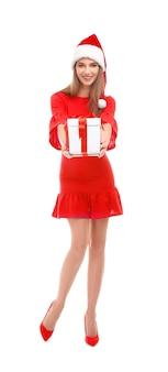 Piękna młoda kobieta w santa hat trzyma pudełko na białym tle