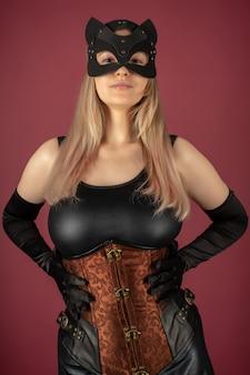 Piękna młoda kobieta w skórzanym gorsecie i pozującej masce kota