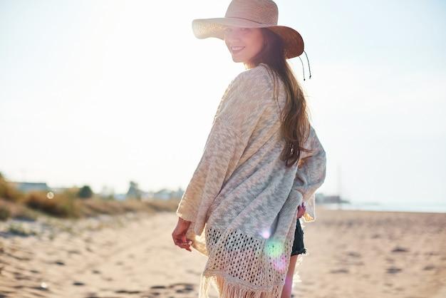 Piękna młoda kobieta w słomianym kapeluszu na plaży