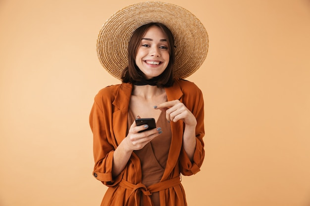Piękna młoda kobieta w słomkowym kapeluszu i letnim stroju stojąca na białym tle nad beżową ścianą, korzystająca z telefonu komórkowego