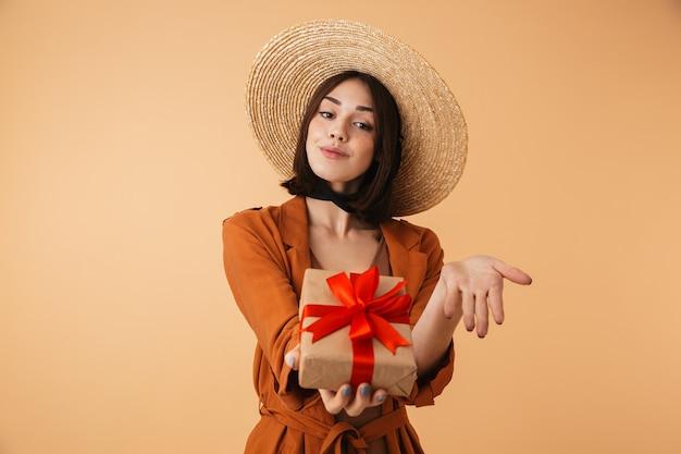Piękna młoda kobieta w słomkowym kapeluszu i letnim stroju stojąca na białym tle nad beżową ścianą, pokazując pudełko na prezent
