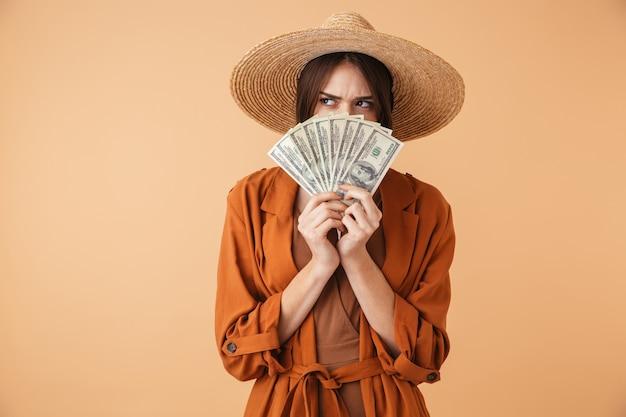 Piękna młoda kobieta w słomkowym kapeluszu i letnim stroju stojąca na białym tle nad beżową ścianą, pokazująca banknoty pieniędzy