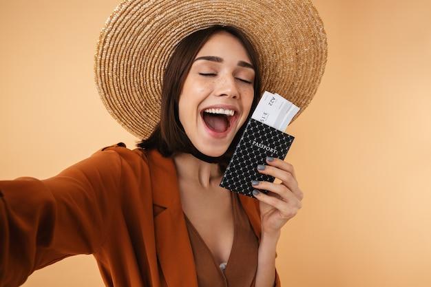 Piękna młoda kobieta w słomkowym kapeluszu i letnim stroju stojąca na białym tle nad beżową ścianą, robiąca selfie trzymając paszport z biletami lotniczymi