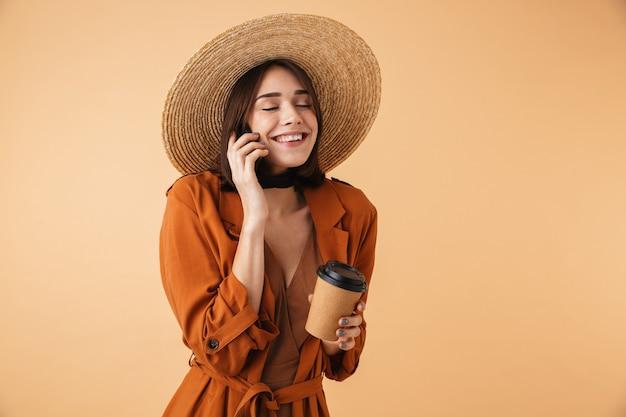 Piękna młoda kobieta w słomkowym kapeluszu i letnim stroju stojąca na białym tle nad beżową ścianą, trzymająca filiżankę kawy na wynos, używająca telefonu komórkowego