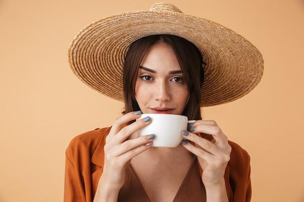 Piękna młoda kobieta w słomkowym kapeluszu i letnim stroju stojąca na białym tle nad beżową ścianą, trzymająca filiżankę